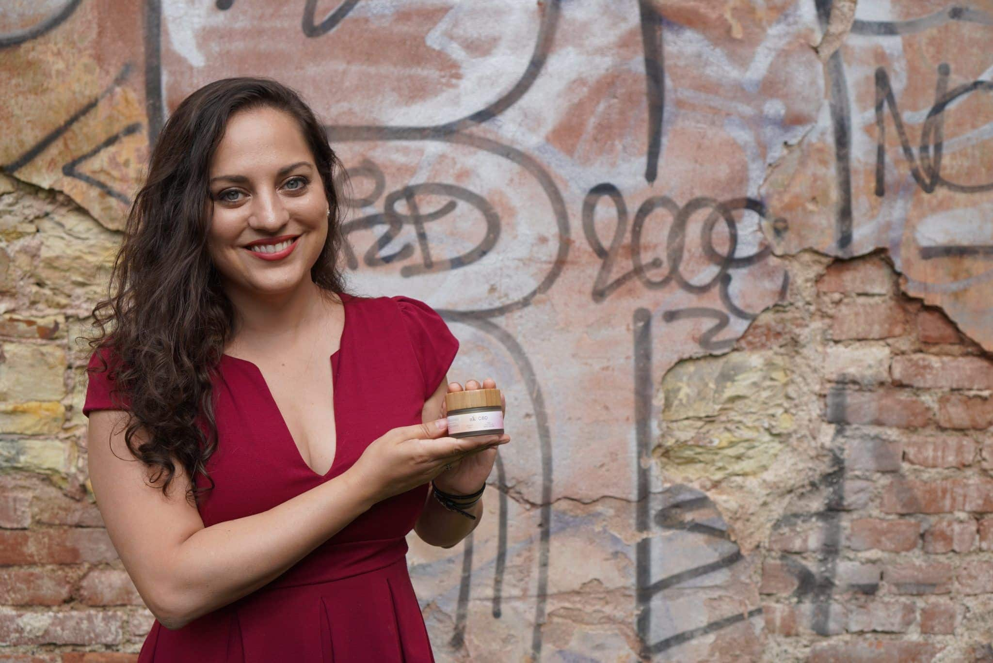 Kate wears a red dress and stands in front of a pink graffitied wall holding a jar of soothing salve.