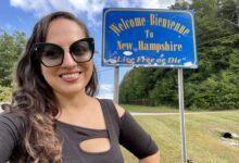 """Kate wears sunglasses and a black shirt with cutouts and stands in front of a side reading """"Welcome-Bienvenue to New Hampshire. Live Free or Die."""""""